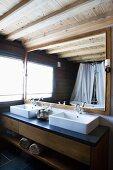 Modern washstand with twin basins below framed mirror in bathroom with rustic, modern ambiance