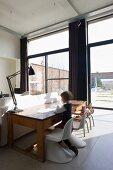 Wohnzimmer mit durchgehender Fensterfassade in einem umgenutztem Schulhaus - Panton Chairs kombiniert mit alter Schulbank und Stühlen