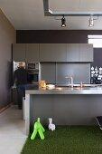 Mann vor offener Kühlschranktür in Designerküche mit Edelstahl-Arbeitsfläche und HPL-Front; im Vordergrund Spieltiere auf Kunstrasenteppich