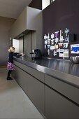 Mädchen an der langen Arbeitsfront einer Designerküche aus grauem HPL und Edelstahl; angepinnte Erinnerungsstücke an der Wand