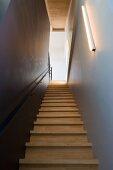 Schmaler Treppenaufgang aus Gummibaumholz mit Beleuchtung durch schlichte Linestra