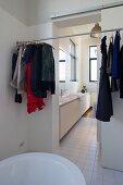 Verschiedene Kleidung an einer Stange und Blick auf langen Waschtisch im angrenzenden Raum