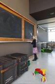 Offener Wohnraum mit alter Wandtafel in umgenutztem Schulhaus; alte Transportkisten und buntes Holzrad auf poliertem Betonboden