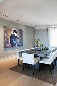Weissbezogene, gepolsterte Stühle an hellgrauem Tisch gegenüber grossformatigem Bild an grauer Wand in modernem Esszimmer