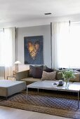 Couchtisch auf traditionellem Teppichläufer vor Polsterhocker und Sofa in modernem Ambiente