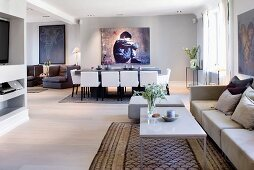 Moderne Loungeecke vor Essplatz mit weissen, gepolsterten Stühle und grossformatiges Bild an grauer Wand in offenem Wohnraum