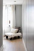 Selbstgebauter Sessel mit Kissen auf Holzboden vor grauem Einbauschrank und Fenster mit luftigem Vorhang