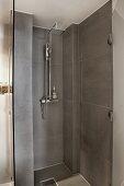 Moderner Duschbereich mit grauen Fliesen und offener Glastür