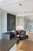 Dunkle Sessel vor grauer Wand mit Tiermotiv auf Bild in grossräumigen, modernen Wohnzimmer