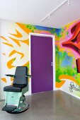 Corner of room with graffito mural and vintage dentist's chair on concrete floor
