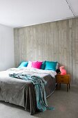 Colourful scatter cushions on double bed in modern bedroom with exposed concrete wall and concrete floor