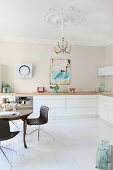 Antique dining table and modern chairs in renovated kitchen with stucco elements on walls and ceiling