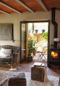 Sitzwürfel mit Fellbezug auf Teppich und Kanonenofen mit Feuer neben offenen Terrassentüren im Wohnzimmer eines Landhauses