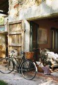 Fahrrad mit Korb vor rustikalem Natursteinhaus mit Türlade und Blick durch offene Terrassentüren auf Polstersofa