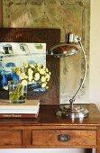 Retro Tischleuchte mit Chromgestell neben Blumenstrauss auf schlichtem Wandtisch vor gerahmtem Bild mit Architekturmotiv
