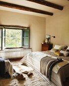 Gemütliches Bett mit Tagesdecken und verschiedenen Kissen vor offenem Fenster im Schlafzimmer mit Holzbalkendecke