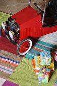 Blick auf rotes Kinderfahrzeug im Vintagestil und Spielzeug auf gestreiftem Teppichläufer