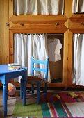 Blauer Kinderstuhl und blauer Tisch vor Holzschrank mit Vorhängen in den Öffnungen