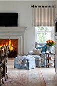 Upholstered armchair and footstool next to blazing open fire