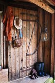 Leather jacket and ladies' hat hanging on board door of woodshed next to hacksaw and lantern