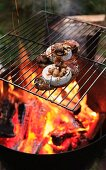 Bread topped with goat cheese, trumpet chanterelle mushrooms and nuts on grille over brazier