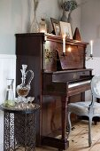 Delicate metal side table next to piano with lit candles in sconces mounted on front in corner