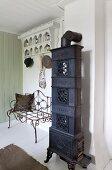 Antique stove next to delicate metal bench below coat rack in wood-clad foyer