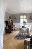Set table opposite piano in spacious dining room with rustic wooden floor and white wooden ceiling