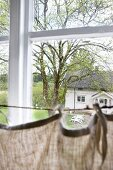 Curtain hanging from rope stretched across lattice window and view into garden of traditional country house
