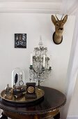 Collection of antique objet on brass tray and candelabra on side table; deer's head on wall