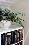 Dried flower arrangement in ceramic vessel on simple, white bookcase