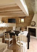 Black dining table and simple wooden chairs in front of open, corner fireplace in rustic kitchen with stone wall