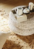 Espresso cup on tray on white, rattan pouffe and sisal rug