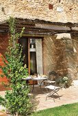 Set table on sunny terrace of Mediterranean stone house