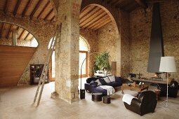 Modern seating area with open fireplace in Mediterranean stone house