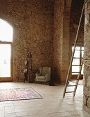 Wing-back armchair and coat rack in corner of high-ceilinged, restored, Mediterranean-style stone house