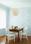 Breakfast table and white, wooden chairs beneath a round, wicker hanging lamp in the corner with bright blue wall paper with a white floral pattern