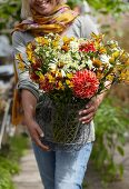 Woman carrying summer bouquet of dahlias, alstroemeria, chamomile and rudbeckia