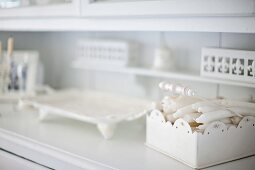 Box of white candles and serving dish on kitchen dresser