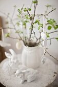 Easter eggs and white ceramic hearts hanging from twigs in jug on small table next to white ceramic Easter bunnies