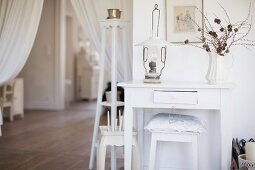 Oil lamp and vase of twigs on console table, cushion on stool in living room