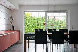 Designer Esszimmer mit Essplatz vor Terrassenfenster und Gartenblick