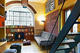 Loft-style interior with half-height shelving below arched window and grey leather sofa against brick wall