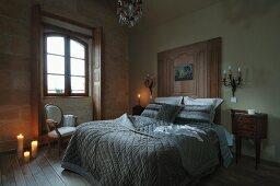 Doppelbett mit moderner, steingrauer Tagesdecke im Kontrast zur Holzvertäfelung am Kopfende, antiken Kleinmöbeln und Wandleuchtern im Rokokostil