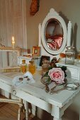 Silver-plated hand mirror, perfume bottles and rose on antique, shabby-chic dressing table