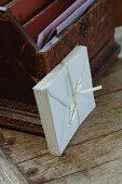 Kuverts mit Seidenbändchen zusammengehalten und an antike Briefschatulle gelehnt