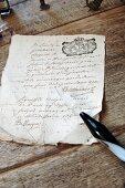 Verknittertes historisches Schriftstück und Glasfederhalter auf antikem Naturholztisch