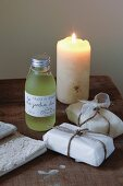 Small bottle of massage oil with label written in French and packaged soaps next to lit candle