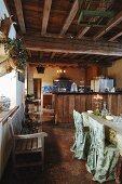 Stilistische Gegensätze in rustikaler Wohnküche - mit edlen Stoffen drapierter Essplatz unter grober Holzdecke