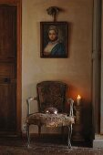Antique portrait of woman above Rococo chair with worn fabric upholstery